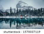 Small photo of Wooden lodge in pine forest with heavy snow reflection on Lake O'hara at Yoho national park, Canada