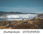 Greenland Glacier with Sea Ice and a Glacial Landscape near the Eqip Sermia Glacier, Eqi in Western Greenland near arctic town of Ilulissat. Blue sky on a sunny day. Calving Glacier.