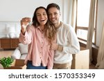 Small photo of Happy young family couple holding key to new home on moving day concept, first time real estate owners man husband embrace woman wife look at camera proud buying property stand in own flat with boxes