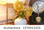 Small photo of a table lamp shining on a beautiful yellow rose and small white flowers set in the background is a old windup chiming clock with a pendulum