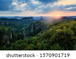 Carolafelsen in Germany, beautiful evening view over sandstone cliff into deep misty valley in Saxony Switzerland. Sandstone peaks increased from foggy background. Evening landscsape in wild nature.