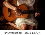 Young Woman Playing Guitar Wit...