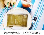 Authentic tamale stuffed with chicken and green sauce on a plate wrapped in a banana leaf by a cup of hot chocolate and a pile of traditional green tamales in corn leaves.