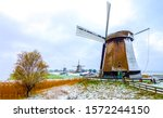 Windmill farm in autumn snow. Snowy windmill farm in Netherlands. Windmill farm in snow autumn. Windmill farm snow landscape