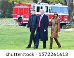 Small photo of WASHINGTON, DC - NOVEMBER 26, 2019: President Donald Trump, First Lady Melania Trump and their son Barron walk across the South Lawn in front of a Red Fire Truck to Marine One on their way to Florida.
