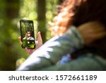 A young woman with reddish hair is taking selfies with her mobile phone in an summer forest of green and other colors in Macedonia Greece.