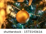 Small photo of Christmas tree with gold bauble ornaments. Decorated Christmas tree closeup. Balls and illuminated garland with flashlights. New Year baubles macro photo with bokeh. Winter holiday light decoration