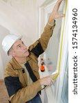 Small photo of portrait of workman measuring window