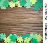 Small photo of Happy Saint Patrick's mockup of handmade felt shamrock clover leaves on wooden background.