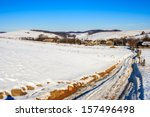 road along a snow-covered mountain slope leading to the old village in winter - stock photo