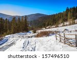 wooden fence near the road leading to the forest in the winter mountains in good weather - stock photo