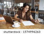 Small photo of Business, gig economy concept, Charming young brazilian female entrepreneur sitting co-working cafe, reading working paper, taking notes, using laptop as working remote from office, drink cappuccino