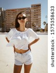 Small photo of girl in sunglasses, akimbo, posing for the camera on the background of buildings on the beach sand