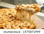 Small photo of Stock image of Very cheesy pizza slice .Pizza is a savory dish of Italian origin, consisting of a usually round, flattened base of leavened wheat-based dough topped