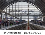 """Small photo of FRANKFURT, HESSE / GERMANY - Nov 20, 2019: View into hall of the main station. In the back an arch made of glass & steel with writing """"Frankfurter Allgemeine"""". Passengers waiting at the platforms."""
