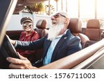 Happy senior couple having fun on new convertible car - Mature people enjoying time together during road trip vacation - Elderly lifestyle and travel transportation concept - stock photo