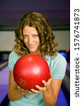 Small photo of Woman in a bowling alley, holding a red bowling ball