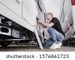 RVing Theme. Caucasian Men in His 40s Preparing His Travel Trailer For the Season Inside RV Storage. Looking Inside Refrigerator Compartment. - stock photo