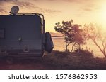 Scenic Sea Front RV Park Spot. Camper Van with Satellite TV Antenna. Vacation Road Trip in a Motorhome. Recreational Vehicle Theme. - stock photo
