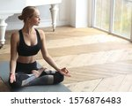 Small photo of Harmonize yourself. Smiling yoga girl sitting in lotus pose at yoga studio, looking at window, copy space