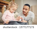 Small photo of Portrait of young stay at home dad reading books with cute little daughter while enjoying tine together in home interior