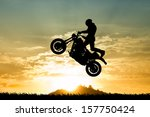 Постер, плакат: stuntman motorcyclist at sunset