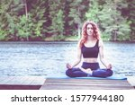 Small photo of Beautiful girl in a yoga pose on the lake. Lotus position , Padmasana. The concept of appeasement, healthy lifestyle. Space for text