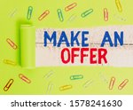 Small photo of Text sign showing Make An Offer. Conceptual photo Proposal Bring up Volunteer Proffer Bestow Bid Grant Paper clip and torn cardboard placed above a wooden classic table backdrop.