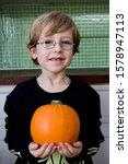 Little Boy Holding An Orange...