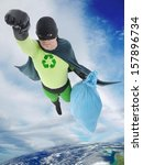 Green superhero flying away from Earth with bag of trash helping to keep the planet clean. Elements of this image furnished by NASA - stock photo