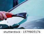 Small photo of Scraping ice off car windscreen