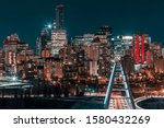 Long exposure of the Edmonton Alberta city skyline at night. The illuminated Walterdale bridge is in the foreground. Vehicle traffic is visible in the light streaks. Blue and Orange tones.