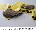 Small photo of Close up of pieces grey asbestos and fibers. Old roof tiles and yellow barrier tape. Warning: caution health effects, hazard. Asbestos removal. Asbestosis or mesothelioma, part of a serie.