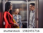 Small photo of The girls and the guy ride in the elevator. Students go to study. People in the elevator. Elevator with people, communication in public places. Colleagues go to work in the elevator.