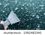 Small photo of Scraping ice from car windshield