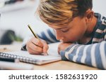 Small photo of Student drawing with pencil on the notebook. Boy doing homework writing on a paper. Kid hold a pencil and draw a manga at home. Teen drawing sitting at the table. Education art talent ability concept.