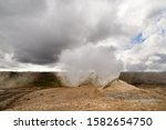 Small photo of Volcanic landscape with a large fumarole that emits a lot of steam, contrasting sky with a little blue as well as white and grey clouds - Location: Iceland, Hochland