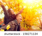 happy couple in autumn park.... | Shutterstock . vector #158271134