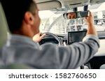 Responsible Caucasian car driver shifting rear-view mirror. Photo taken from backseat. - stock photo