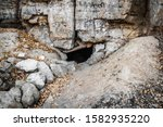 The narrow entrance to the mysterious karst cave. - stock photo