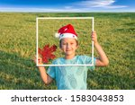 Small photo of The background is green lawn. Charming boy in a clownish cap of Santa Claus smiles through a white frame. The toy is a red and gold maple leaf. Concept portrait and advertising photo