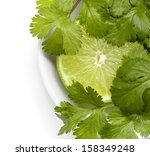 Lime and cilantro or coriander in small white bowl. - stock photo