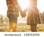 Stock photo young couple in love walking in the autumn park holding hands looking in the sunset 158352050