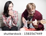 Small photo of Young woman with trepidation and admiration listens as her boyfriend plays the electronic guitar.
