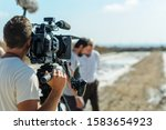 Small photo of videographer with tripod camera in documentary film shooting