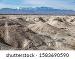 USA, Nevada, Clark County, Tule Fossil Beds National Monument: White gypsum hills at the urban fringe along the Las Vegas Wash with Mt. Charleston in the distance.