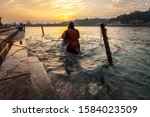 Small photo of Two woman taking a dip in river Ganga at sunset. Dipping is a ritual infused with religious beliefs. The water of this holy river is meant to absolve people of their sins
