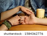 Small photo of Hands of a woman palmist fortunetelling a young man