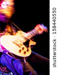 motion blur abstract of a rock guitarist with a golden guitar - stock photo