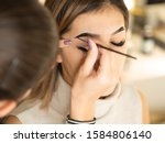 Small photo of Eyebrow tinting. Close up master applying brow tint with a brush. Cosmetic procedures, eyebrow permanent makeup